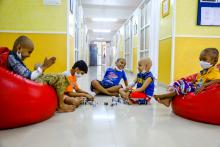 Children going through cancer treatment, wearing face mask and bald head sitting in red bean bags, playing together