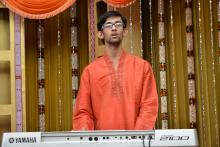 Image: Adithya Venkatesh, autistic music prodigy in a red kurta on stage playing Carnatic music on his keyboard