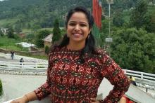 Aditi who has Fibromyalgia in an outdoor balcony setting in a red printed full sleeved dress