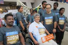 Jacqueline Colaco on a wheel chair, in white at the TCS 10K with some of the other participants