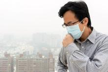 Image of a man with a mask in a polluted city.