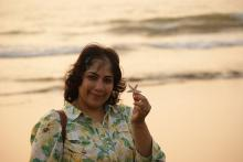 Picture of the author Smriti Joshi holding a starfish and set against the sea
