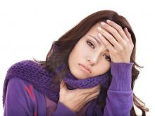 Woman in purple sweater and muffler holding her head and neck in distress
