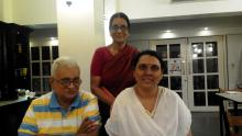 Family pic inside a room of a young woman with a white dupatta seated with her silver haired father in a striped green and yellow t-shirt on the left and her mother standing behind them in a red sari and blouse