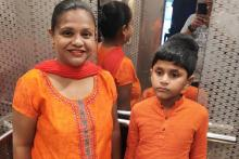 Barnana with her son who is on the autism spectrum. Both are in orange and behind them are blurry reflections in the mirror