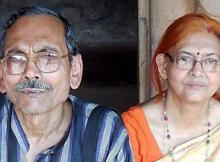 An elderly and spectacled couple Mr Pranab Basu in a blue striped shirt with his wife in an orange blouse and a cream sari