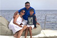 Pooja in a white dress with  her son and husband on the deck of a ship