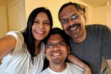 Image description: Pratyush a young dark haired Indian man in a white t-shirt in the centre with his mom on the left in a white top taking the selfie and his spectacled father on the right in a grey shirt