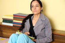 Image: Stock pic of a woman wearing a grey jacket, light blue pants staring in front with nooks lined up behind her