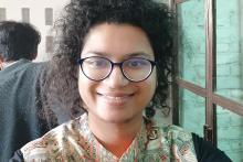 A woman wearing specs looking straight at the camera