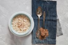 A pic of a bowl of oats porridge with spoons on the right with flax seeds spilling over