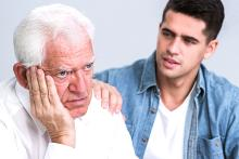 Image of an older silver haired person thinking and a younger dark haired person in a blue shirt and white t-shirt sitting next to him and debating whether to share or not about Parkinson's Disease diagnosis