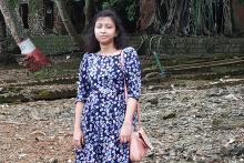 A young woman Ankita Bardhan standing in a purple and white printed dress in an open setting. The bottom of trees can be seen behind her
