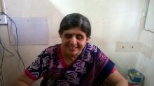 Dipti Bhatia, visually impaired from birth wearing a blue red and pink kurta and dupatta at her desk with wires  visible in the background