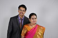 Image: Autistic adult Pranav in a suit with his mother in a red sari and gold border