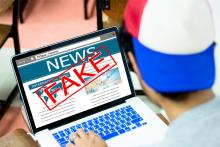 Stock pic with the word FAKE over the news on a laptop