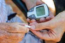 A pair of hands, one holding a glucometer and the other a pill showing support of a caregiver to a diabetic patient