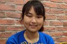 A young woman with bangs and wearing a blue tshirt in front of a red brick wall