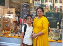 A woman in a yellow kurta standing with her young son in a white shirt in front of a shop window. Both wear spectacles.