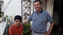 A young autistic boy on the left in a red shirt with his father in a striped blue and white shirt in a home balcony