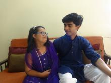 Aarshia on the left a young Indian black haired spectacled girl with Down Syndrome in a purple dress and on the right her brother Aaryamann a young Indian teen boy with black hair in a purple kurta and white pyjamas
