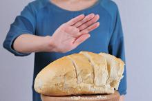 A person in a blue shirt with head cut off holding hand up to say no to a loaf of bread