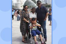 Rishi Chowhan a young child with Duchenne Muscular Dystrophy and Autism on a wheelchair with his family standing behind him from Left to Right- his mother, his sister and his father. Picture shows Singapore's Merlion in the background