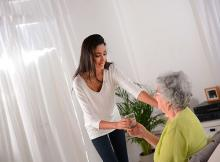 Stock pic of a younger person in a white top and black pant supporting and holding hands with a seated silver haired elderly lady in a green top