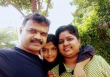 Image of Pavithra, a brain tumor survivor in a green dress with her husband in black and son