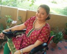 Aarthi Sampath, with limb girdle muscular dystrophy happy and contented on her wheelchair
