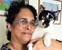 Image: Vidya, with spectacles and black hair holding a black and white on her left shoulder