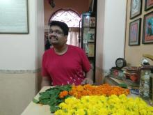 Kabir Kumtha, a young man with autism wearing a red tshirt standing in front of a table and working with yellow and orange marigold or jhendu, his favourite flower to make torans or garlands