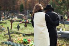 Image: Backs of woman in a white dress with a man in a black suit and black hat in a cemetery mourning passing of a loved one