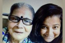 Mausumi, a dark haired woman on the right with her mother, a person with dementia on the left. Mother is wearing specs and  a bindi on her forehead and you can see the blue and white sari draped around her shoulders