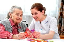 A caregiver in a white dress does an activity with an elderly person with dementia in red and grey