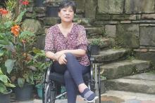 Nagaland Disability Activist and commissioner on a wheelchar in front of a building and some plants