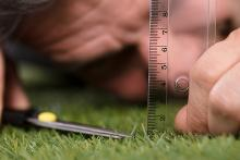 A person measuring the length of grass blades with a ruler and trimming the grass