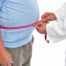 Image: A person with a measuring tape around an expanded waist signifying obesity
