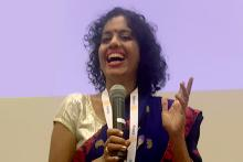 Urmila Prabhu speaking at a Vitiligo forum with a black sari and golden blouse