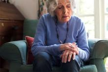 Image: Stock pic of an older silver haired woman in a blue sweater sitting on a sofa and holding hands for an article on living well with Parkinsons Disease