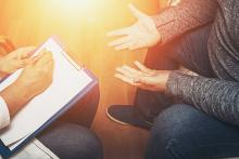 A partially visible counsellor sitting with a person with outstretched hands
