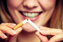 Stock pic of the bottom half of a woman's face smiling and breaking a cigarette as she tells her experience of how she quit smoking