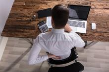 Stock pic of the back of a man feeling rheumatic pain while working at his desk on a laptop