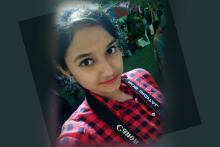 A selfie pic of a young woman in a black and red checked shirt and a camera bag strap visible around her neck
