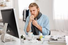 Image: Man at a work desk coughing with some medicine on the desk