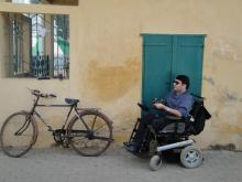 Rustom Irani on the right in a wheelchair in front of a blue door and on the left is a wheelchair against a wall