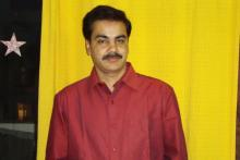 Image: Sanjay Jaiswal, with black hair and a moustache is an Oral Cancer survivor and stands in a red shirt against a yellow background