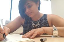 Image of Ekta, in a black dress, short black hair journaling as part of her self care routine