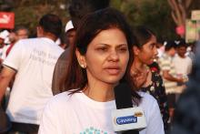A young woman in the foreground in a white t-shirt talking into a mic