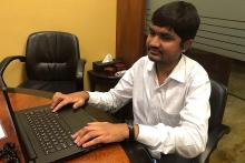 A visually impaired young man in a white shirt working on his computer at a desk in an office
